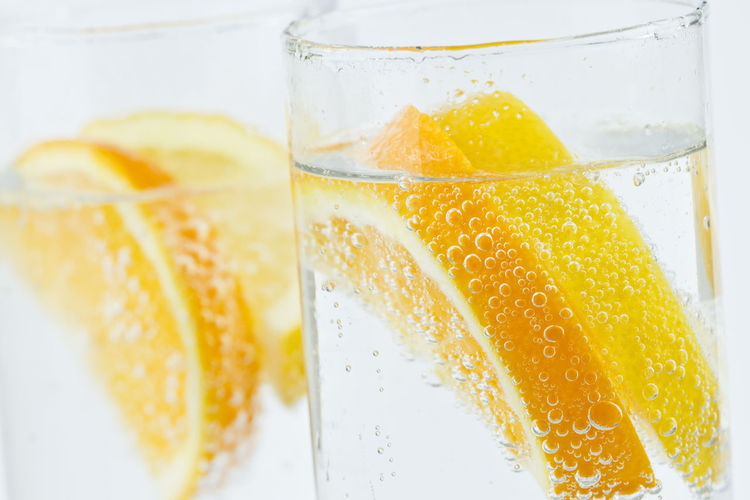 Close-Up Of Lemon Slices In Glasses Against White Background