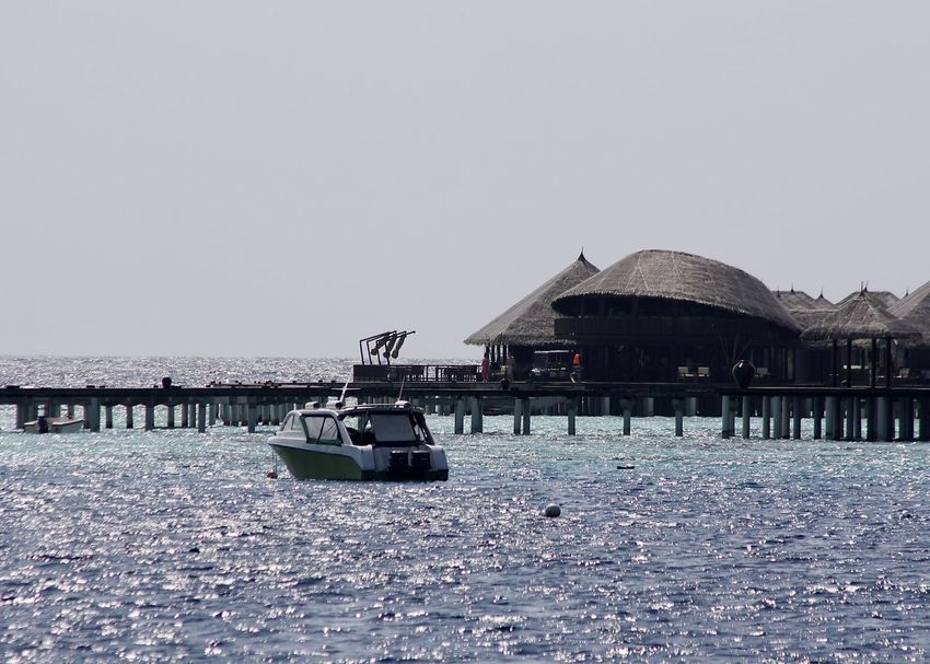 Architecture Blue Boat Building Exterior Built Structure Clear Sky Day Enjoying Life Jetty Maldives Nature No People Outdoors Pier Politics Reflection Sea Sky Stilt House Sunshine Travel Travel Destinations Vacations Water Watervillage
