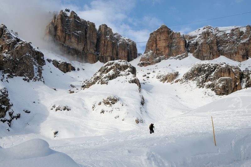 People Climbing On Snowcapped Mountains Against Sky