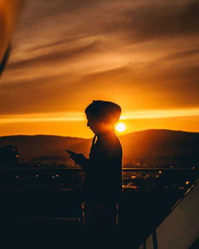 Silhouette man standing against orange sky during sunset