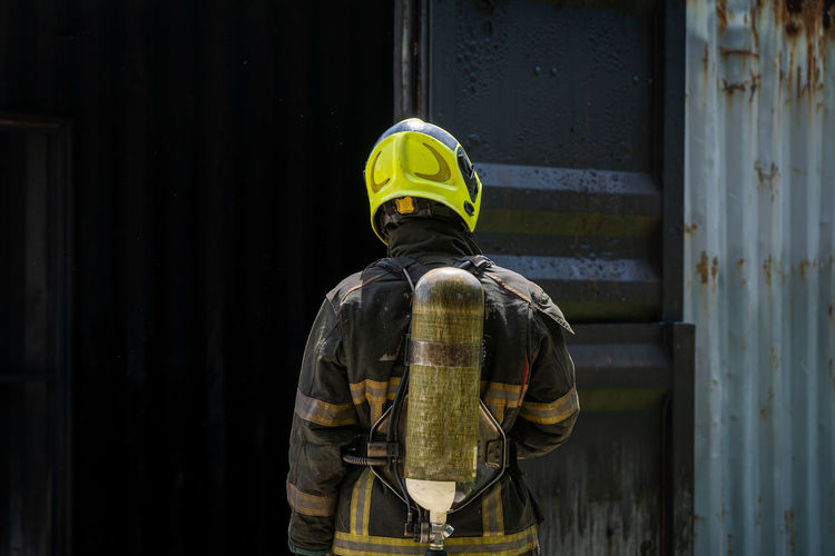 Fireman wearing suit for safety using water and extinguisher to fighting with fire flame.