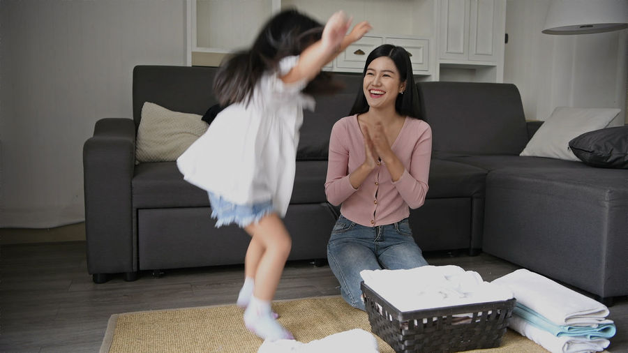 Two People Women Sofa Furniture Indoors  Home Interior Adult Emotion Lifestyles Young Women Full Length Domestic Room Young Adult Sitting Real People Front View Togetherness Leisure Activity Living Room Casual Clothing Flooring Sister