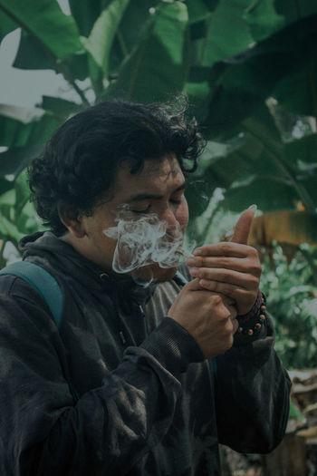 Portrait of teenage boy holding leaf