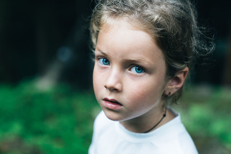 Close-up portrait of cute girl with blue eyes