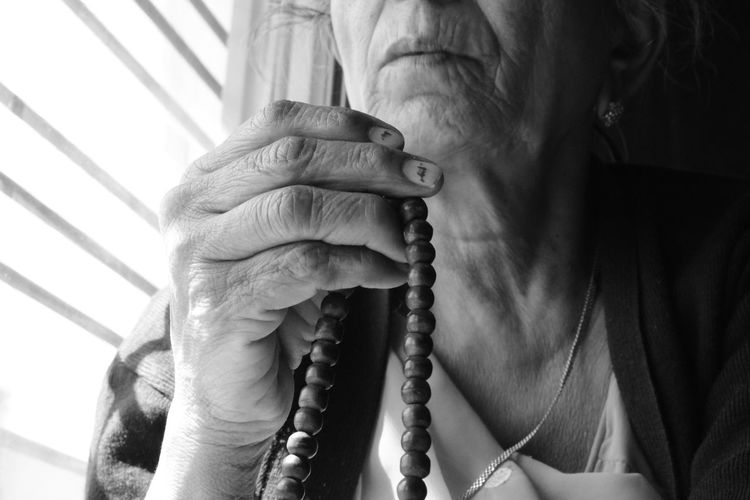 Midsection of senior woman holding bead necklace