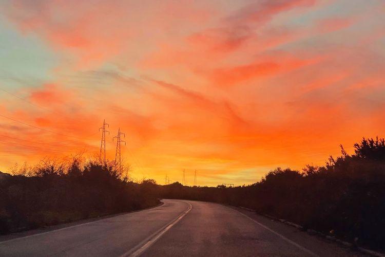 Road by silhouette trees against orange sky