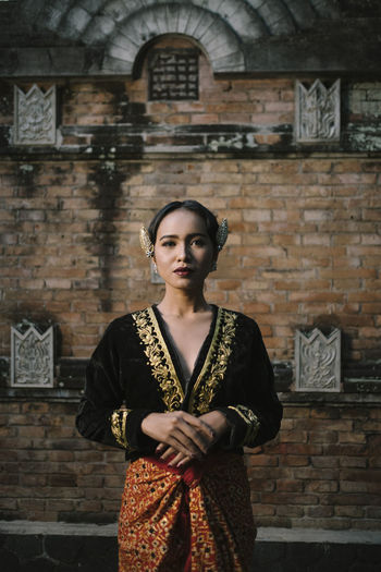 Portrait of woman in traditional clothing standing against building