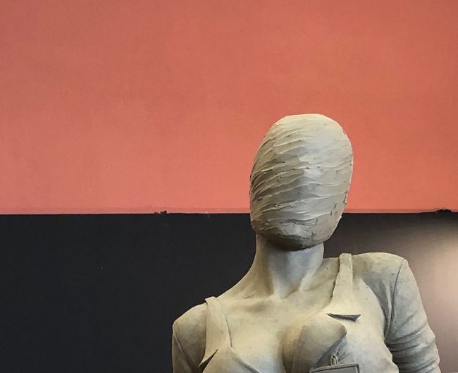 Close-up of statue against red wall