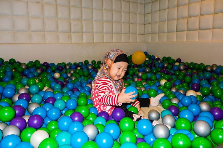 Girl wearing hijab playing in multi colored ball pool