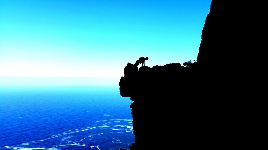 Silhouette Man Exercising On Cliff By Sea Against Clear Blue Sky