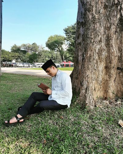 Side view of young man reading book while sitting on grass