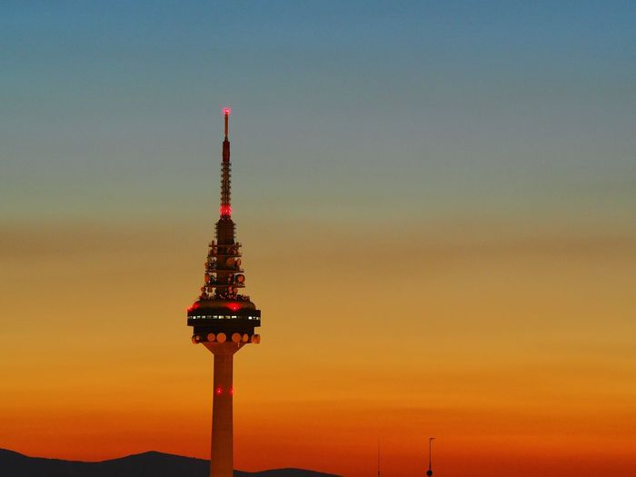 Communication tower against sky during sunset