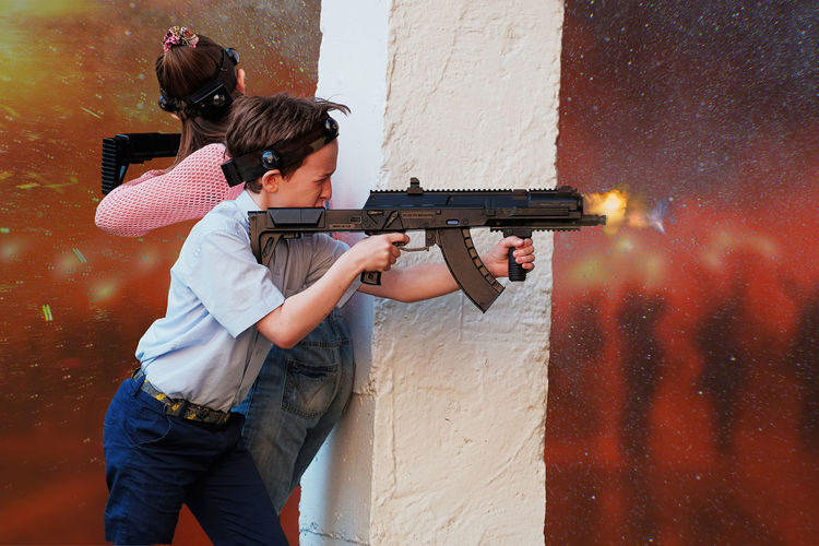 Friends shooting with toy rifles by wall