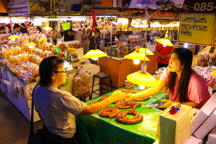 Woman Buying Sausage From Female Vendor At Market Stall During Night