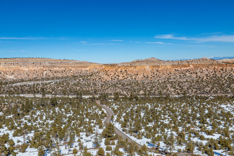A snowy landscape in new mexico with a blue sky overhead
