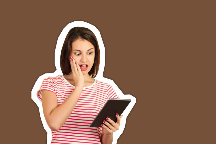 Portrait of young woman using smart phone against gray background