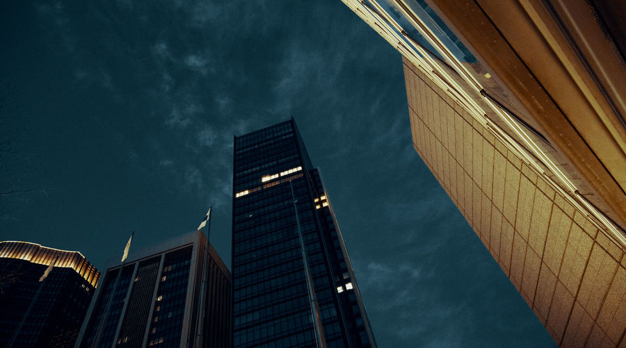 Low angle view of modern buildings against sky at night