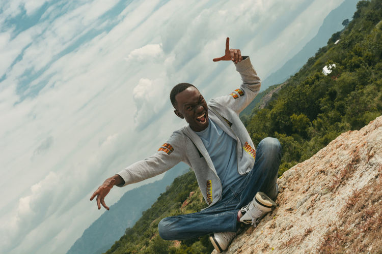 A man showing positive emotion on top of a hill