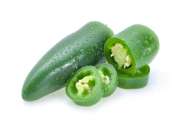 Close-up of wet jalapenos over white background