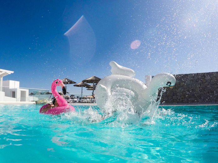 Inflatable rings splashing water in swimming pool against blue sky
