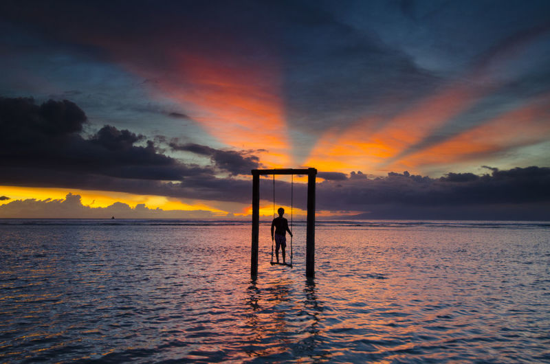Silhouette man swinging over sea against cloudy sky during sunset