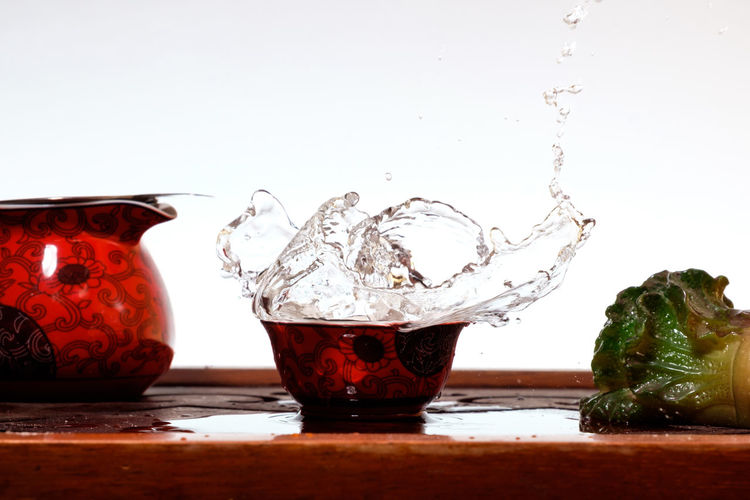 Close-up of water splashing on table against white background