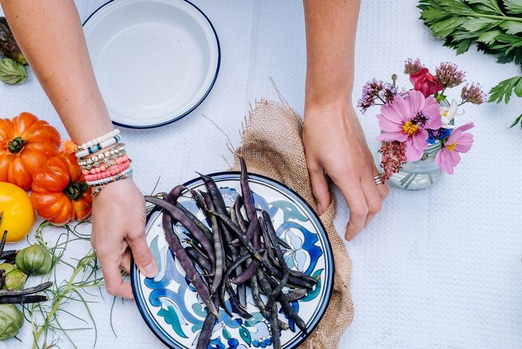 Cropped hands of woman with beans and flowers on table