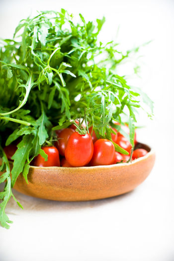 Close-up of fresh herbs and tomatoes in bowl on white background