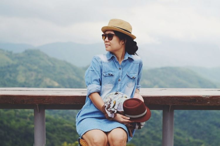 Young woman wearing sunglasses and hat at observation point against mountains