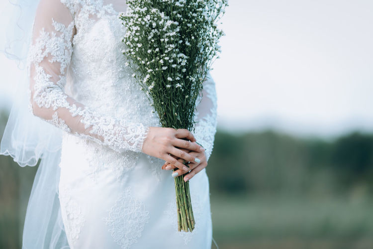 Midsection of bride holding bouquet while standing outdoors