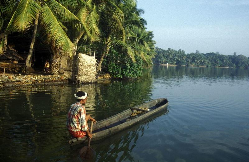Man Rowing Boat In Lake Against Sky