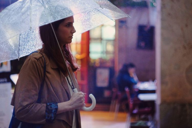 Side View Of Woman With Umbrella Walking On Street During Monsoon