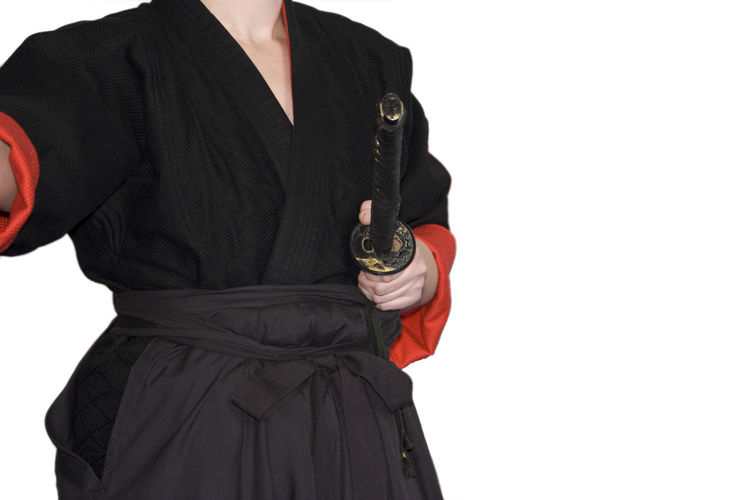 Midsection Of Man In Traditional Clothing With Weapon Standing Against White Background