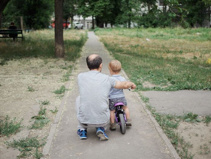 Rear View Of Father Teaching Son To Ride Bicycle On Footpath