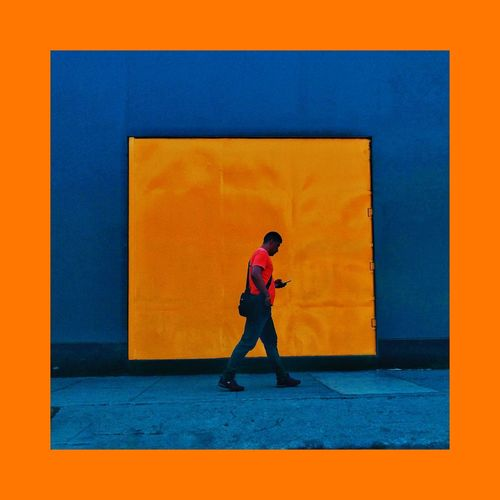 Side view of man standing against orange wall