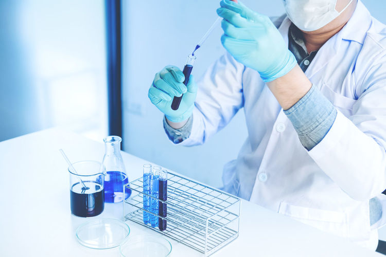 Midsection Of Scientist Doing Experiment In Laboratory