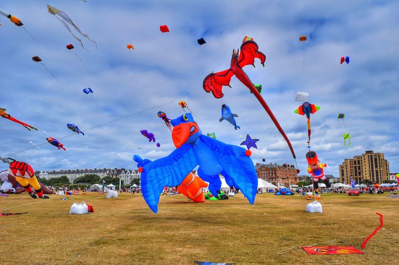 Various kites at ground during festival against cloudy sky