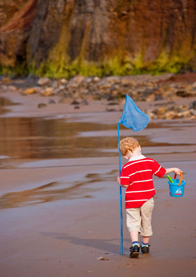 Boy with fishing net walking at beach