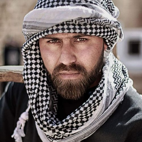 Portrait of serious bearded man wearing headscarf