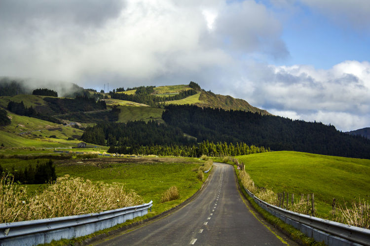 Rural road leading through green hills Asphalt Azores Country Field Grass Green Color Rolling Landscape Rural Scenic Travel Trip Cloud - Sky Direction Environment Green Island Hill Landscape Nature No People Non-urban Scene Outdoors Remote Road Road Trip Scenics - Nature