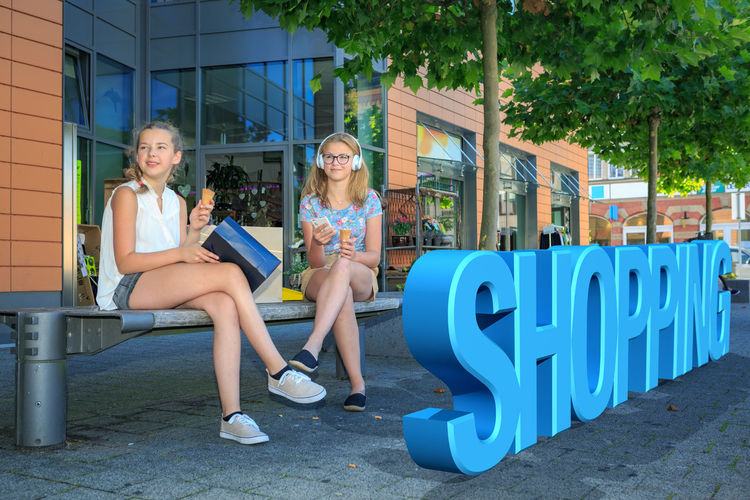 two teenage girls with ice cream during a shopping trip in the city City, Bags, Beautiful, Buyer, Buying, Carrying, Casual, Clothing, Consumer, Customer, Cute, Elegant, Fashion, Female, Feminine, Fun, Girl, Goods, Happiness, Happy, Joy, Leisure, Lifestyle, Looking, Mall, Merchandise, Modern, Portrait, Pretty, Product, Pur Architecture Building Exterior Built Structure Casual Clothing Communication Day Full Length Lifestyles One Person Outdoors Real People Sitting Smiling Text Tree Young Adult Young Women