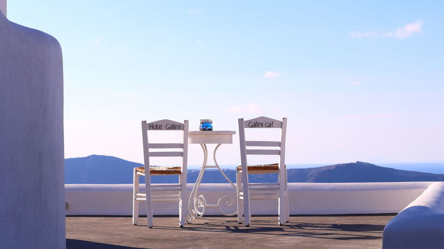 Empty chairs and tables by sea against sky