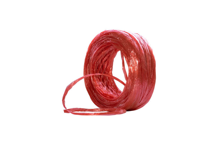 Row of red plastic rope for binding various items isolated on white background. Studio Shot White Background Red Indoors  Close-up Cut Out Copy Space Still Life Single Object No People Thread Rolled Up Shape Spiral Geometric Shape Flexibility Circle Temptation Object Circle Rope Industrial