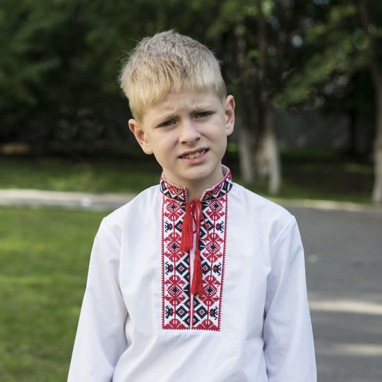schoolboy in Ukrainian embroidery traditional shirt Ukrainian  Blond Hair Boys Childhood Day Elementary Age Embroidery Focus On Foreground Front View Grass Leisure Activity Lifestyles Nature One Person Outdoors Real People Schoolboy Shirt Standing Traditional Young Adult