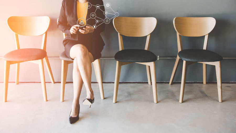 Low section of woman sitting on empty chairs