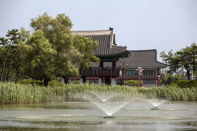 Fountains On Pond By Gazebo In Park Against Clear Sky