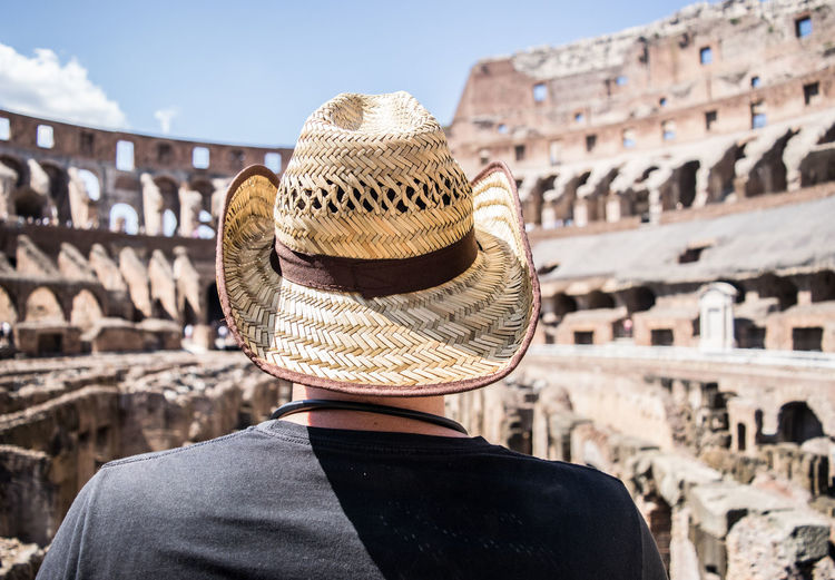Rear View Of Mid Adult Man Wearing Hat Standing Against Old Ruins
