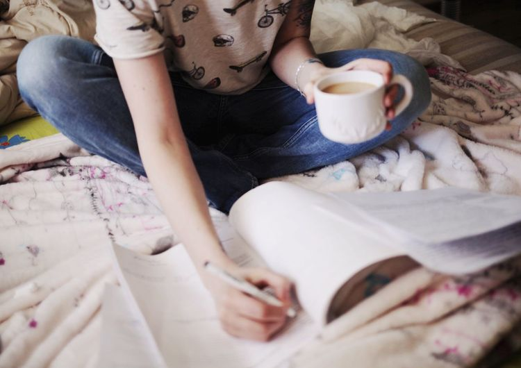 Midsection of woman holding coffee studying while sitting on bed at home
