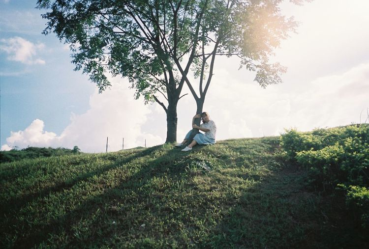 Woman hugging tree while sitting on grassy field against sky