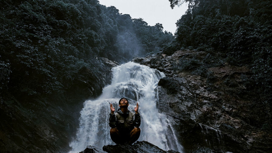 Young man meditating while sitting cross legged on rock against waterfall at forest